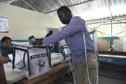A voter casts his ballot at a polling... (AFP) - image 7.0