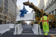 Workers place concrete barricades on a side street... (AP) - image 7.0
