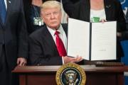 Donald Trump présente aux caméras sa signature sur... (AFP, Nicolas Kamm) - image 2.0