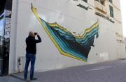 Un passant prend en photo un graffiti réalisé... (AFP, Nezar Balout) - image 2.0