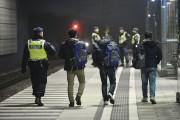 Un policier escorte des migrants dans une station... (REUTERS) - image 2.0