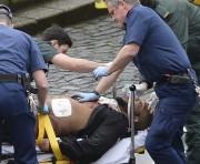 L'homme traité par les ambulanciers serait le suspect... (Photo Stefan Rousseau, PA via AP) - image 1.0