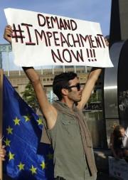 Un manifestant brandit une pancarte demandant la destitution... (Photo Matt Dunham, AP) - image 1.0