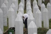 Une femme pleure sur la tombe d'un proche... (AP) - image 2.0