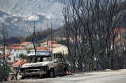 Une voiture calcinée près de la ville de... (REUTERS) - image 2.0