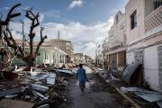 Un homme marche au travers des débris à... (AFP, Martin Bureau) - image 3.0
