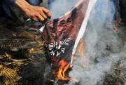 Des musulmans indiens brûlent un portrait d'Aung San... (AP) - image 2.0