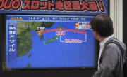 Un passant regarde la trajectoire du missile nord-coréen... (AFP, Kazuhiro NOGI) - image 2.0