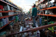 A man stands inside of a destroyed supermarket... - image 1.1