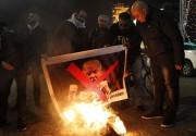 Des manifestants palestiniens brûlent des images de Donald... (AFP) - image 2.0