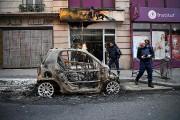 Un policier examine une voiture incendiée par des... (PHOTO ERIC FEFERBERG, AGENCE FRANCE-PRESSE) - image 2.0