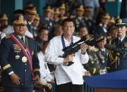 Rodrigo Duterte tient un fusil d'assaut lors d'une... (AP) - image 2.0