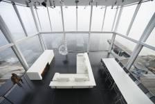 Un cube de verre déposé sur un gros caillou en bordure de lac concrétise le voeu d'un photographe d'unifier dans un même espace sa résidence et son studio.