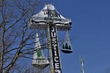Six activistes de Greenpeace ont escaladé la croix du mont Royal tôt mardi matin pour installer une banderole. Le mot «Résolu» et une représentation de la forêt québécoise sont accrochés dans des plateaux, de part et d'autre de l'affiche, afin de représenter la «balance de la justice», explique Greenpeace.
