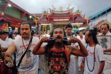 «Une fois que les dieux sont là, on ne ressent rien», assure Jampen Deebuk, après avoir transpercé d'une barre métallique les joues d'un jeune participant au festival végétarien de Phuket, en Thaïlande, rite religieux taoïste à base de mutilations expiatoires.