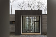Composée de quatre cubes largement vitrés autour d'un volume central, cette résidence secondaire érigée à Potton surplombe le lac Memphrémagog.
