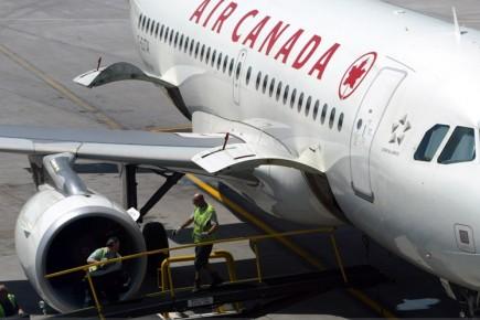 Des employés s'affairent autour d'un avion d'Air Canada.... (Reuters)