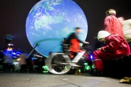 Des passants défilent devant un globe terrestre géant... (Photo AFP)