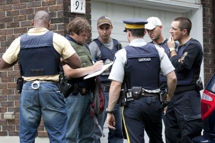 Des policiers discutaient, hier, devant une résidence de... (Photo: PC)