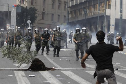Un manifestant lance une pierre aux policiers durant une marche pour protester contre les mesures d'austérité que souhaite adopté le gouvernement de la Grèce.