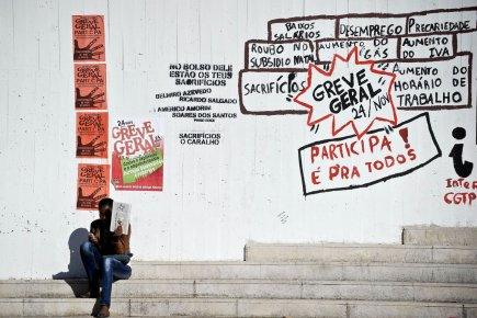 Une femme est assise à proximité d'un graffiti... (Photo: Patricia de Melo Moreira, AFP)