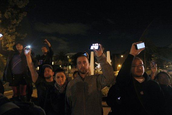 Des gens lèvent leurs appareils Apple à la mémoire du cofondateur d'Apple, dans le parc Dolores de San Francisco. (Photo: Reuters)