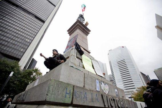 Un manifestant assis près de la statue du square Victoria. (Photo: Marco Campanozzi)