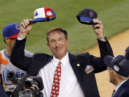Gary Carter brandit une casquette des Expos de Montréal et une casquette des Mets de New York lors du match des étoiles du baseball majeur, au Yankee Stadium, en 2008. (Reuters)