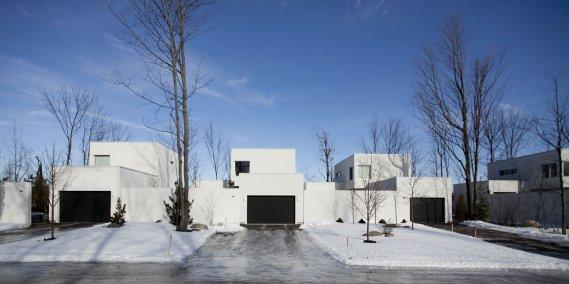 Les maisons en copropriété Haus, à Granby, sont implantées par groupes de trois. Une bande de terrain sépare chaque unité et les portes de garage sont de couleur foncée. Derrière se trouve un terrain boisé à l'état naturel. Notez: les fils électriques sont enfouis et des arbres illuminés à la base du tronc font office de lampadaires. Les maisons sont vendues à partir de 331 000$ (taxes en sus). (Photo: Marco Campanozzi, La Presse)