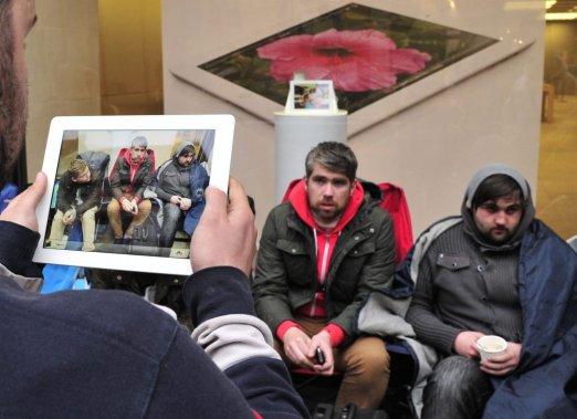 Un homme utilise son nouvel iPad pour prendre en photo des gens qui ont attendu 48 heures en ligne devant le magasin d'Apple... (Photo: Reuters)