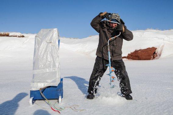 Rosaire Miousse perce un trou à l'aide d'une tarière à glace. (Photo: Édouard Plante-Fréchette, La Presse)