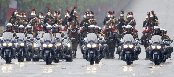 François Hollande, escorté par la cavalerie et les motards de la police, fait un tour présidentiel sur les Champs-Élysées. (Photo: Regis Duvignau, Reuters)
