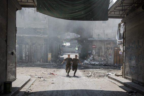 Ville d'Alep, en Syrie. Deux soldats de l'armée syrienne libre tente d'éviter les balles tirées par l'armée de Bachar al-Assad. (Photo Édouard Plante-Fréchette, La Presse)