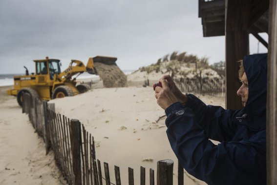 Des employés s'affairent à créer des bancs de sable pour casser les vagues tandis que des résidants immortalisent la mer déchaînée. (Edouard Plante-Fréchette, La Presse)