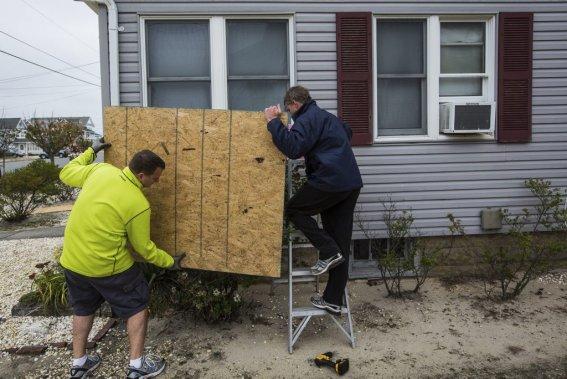 Aux quatre coins de l'île de Seaside au New Jersey, commerçants et citoyens s'affairaient à placarder les fenêtres et à poser des sacs de sable autour des bâtiments lors du passage de La Presse. (Edouard Plante-Fréchette, La Presse)