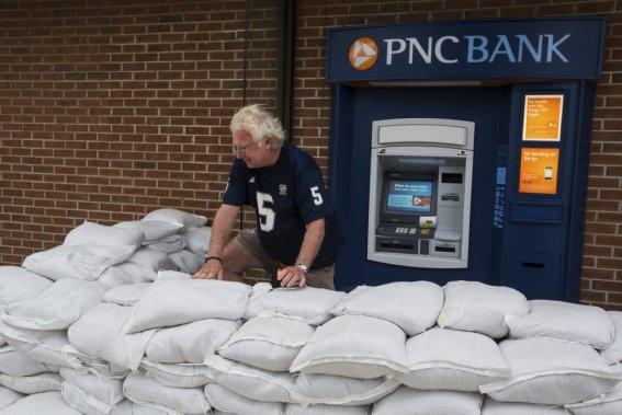 Un dernier retrait au guichet, protégé avec des sacs de sable, pour ce résidant du New Jersey, Bill Mahoney. (Edouard Plante-Fréchette, La Presse)