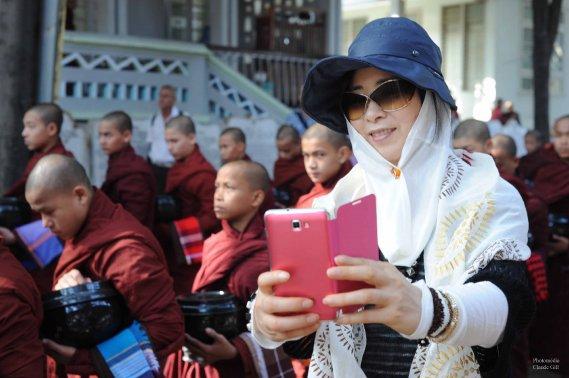Une jolie touriste se prenant elle-même en photo avec les moines en arrière-plan. Amarapura. (Claude Gill)