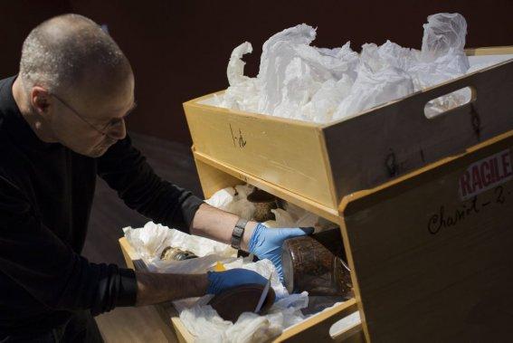 Marcel Marcotte, technicien aux installations, manipule un gobelet cérémoniel en bois peint, en forme de tête de félin de la civilisation inca datant du 18e siècle. (Photo: Édouard Plante-Fréchette, La Presse)
