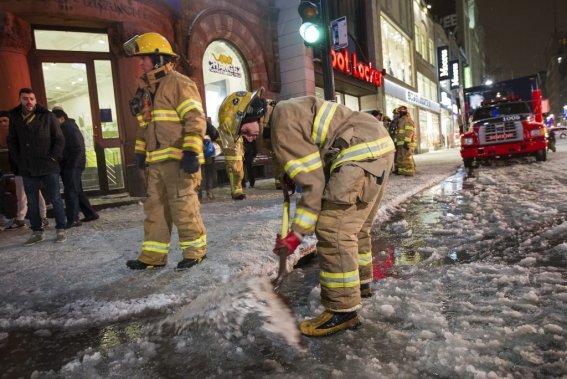 Des pompiers tentent de débloquer une bouche d'égout prise dans la glace. (Edouard Plante-Fréchette, La Presse)