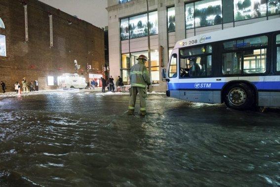 Un pompier guide un autobus de la STM à travers une rue inondée. (Edouard Plante-Fréchette, La Presse)
