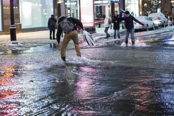 Des passants coincés par l'eau tentent tout de même de traverser malgré le courant et l'épaisse couche de glace. (Edouard Plante-Fréchette, La Presse)