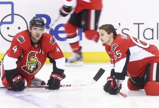 Chris Phillips et Erik Karlsson s'étirent ensemble. (Patrick Woodbury, Le Droit)
