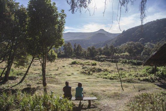 Deux participantes du trek profitent des premiers rayons de la journée, assises devant le premier gîte. (Photo fournie par Emmanuel Leroux-Nega)