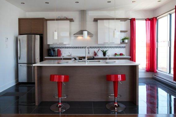 Dans la cuisine, aux plans de travail en quartz, l'évier double sera encastré. La hotte en inox sera aussi incluse. (Photo Robert Skinner, La Presse)