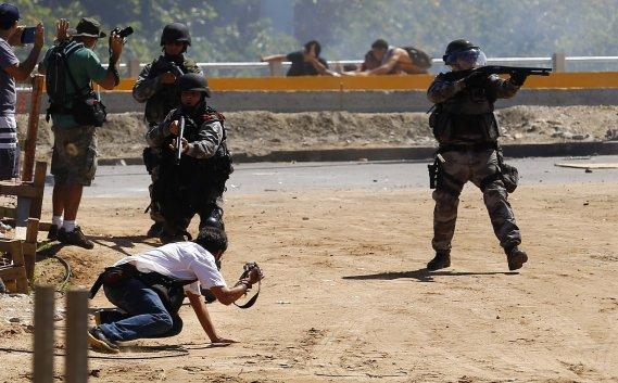 Des policiers d'élite brésiliens mettent en joue des membres de la presse alors qu'ils pourchassent des manifestants aux abords du Stade de Fortaleza (ville de la région du Nordeste) où se jouait un match entre le Brésil et le Mexique dans le cadre de la Coupe des Confédérations, le 19 juin. (PHOTO KAI PFAFFENBACH, REUTERS)