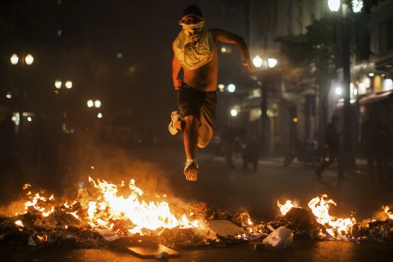 Un manifestant saute par dessus un amas de déchets en feu, lors d'une manifestation à São Paulo, le 18 juin. (PHOTO VICTOR MORIYAMA, REUTERS)
