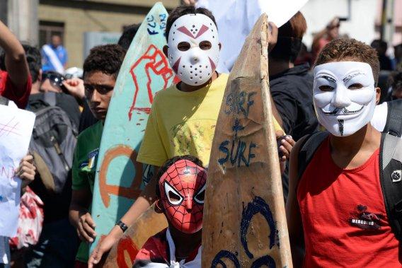 De jeunes surfeurs masqués manifestent à Fortaleza, le 19 juin. Devant les manifestations qui embrasent le Brésil depuis quelques semaines, les médias parlent dorénavant de Printemps tropical. (PHOTO ANDERLEI ALMEIDA, AFP)