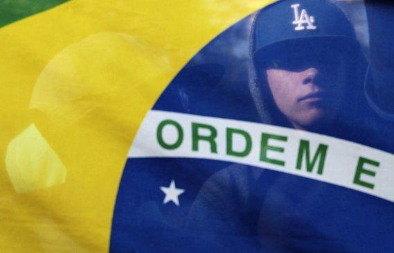 Un manifestant est campé derrière un drapeau brésilien où l'on peut lire en portugais, le mot ordre, à São Paulo, le 19 juin. (PHOTO ALEX ALMEIDA, REUTERS)