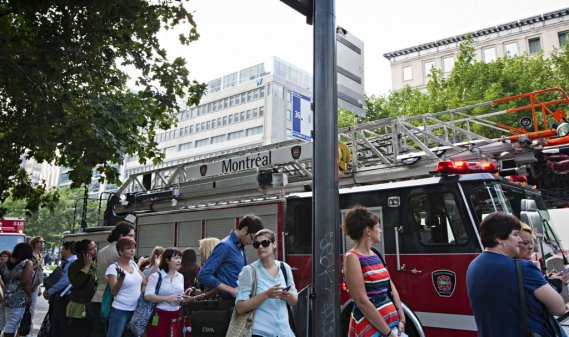 Des Montréalais attendent l'autobus dans une longue file d'attente au Square-Victoria, devant un camion de pompier. Les pompiers venaient de faire évacuer la Tour de la Bourse. (PHOTO ANNE GAUTHIER, LA PRESSE)
