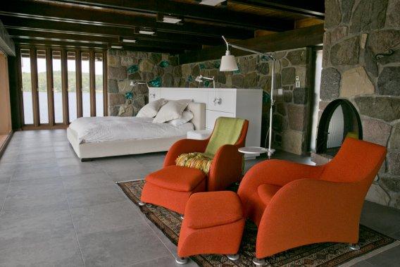 Le pattern est le même partout: céramique, murs, fenêtres, plafonds faits à l'identique. À droite, l'un des nombreux foyers que compte la maison. La vue sur le lac au fond et sur la piscine, au pied du lit. (Photo David Boily, La Presse)